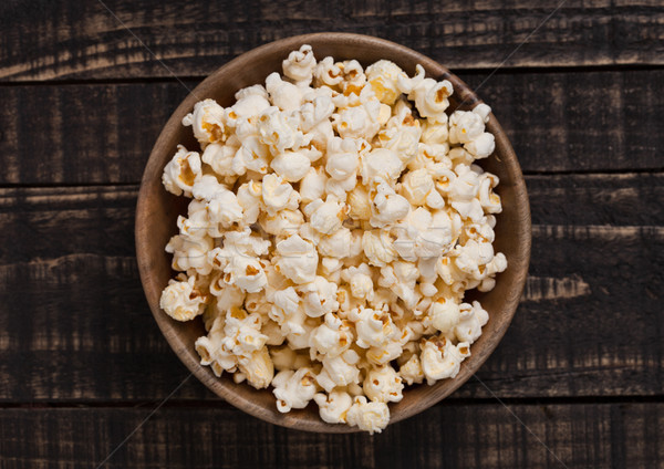 Wooden bowl with fresh salted popcorn on wood Stock photo © DenisMArt