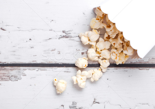 Paper container with fresh salted popcorn on wood Stock photo © DenisMArt