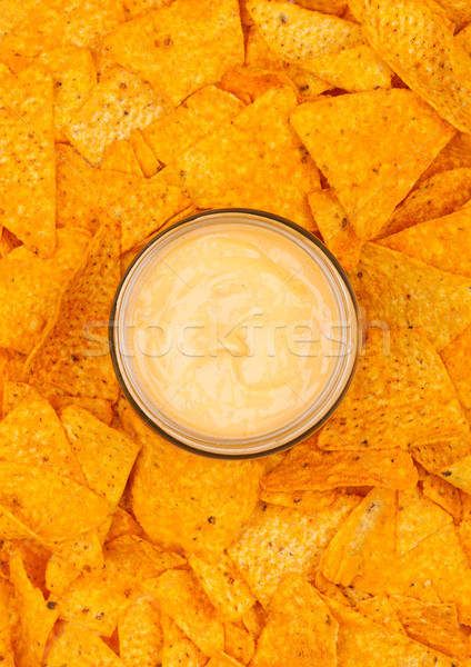 Glass container with cheese dip and nachos chips Stock photo © DenisMArt