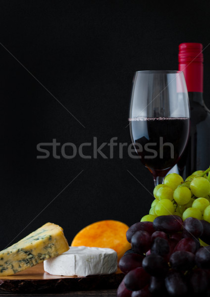 Bottle and glass of red wine with cheese selection Stock photo © DenisMArt