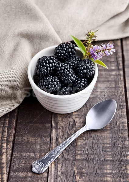 Blackberry in white bowl and spoon on grunge wooden board Stock photo © DenisMArt