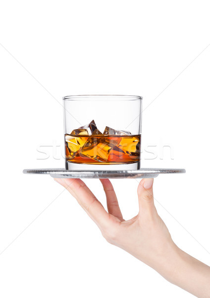 Hand holds tray with glass of whiskey with ice Stock photo © DenisMArt