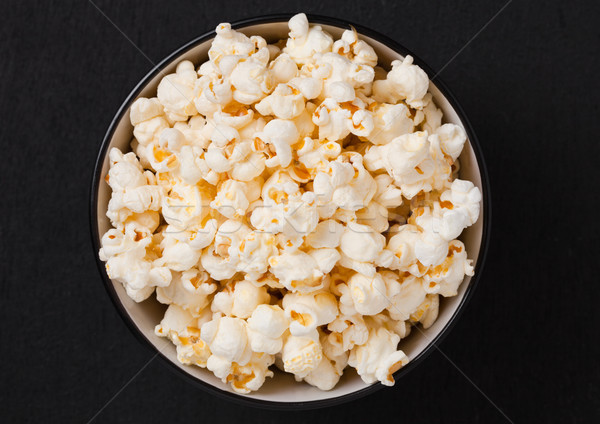 Black bowl with fresh salted popcorn on wood Stock photo © DenisMArt