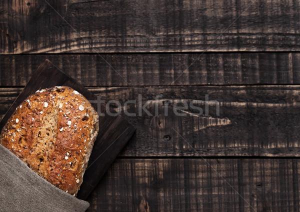 Freshly baked  bread with oats on wooden board Stock photo © DenisMArt