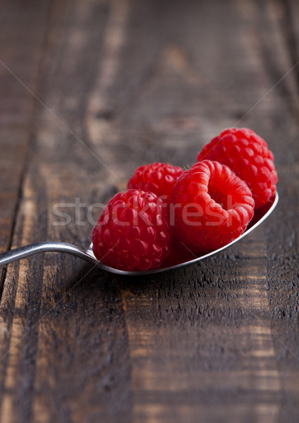 Raspberries on old spoon on grunge wooden board Stock photo © DenisMArt