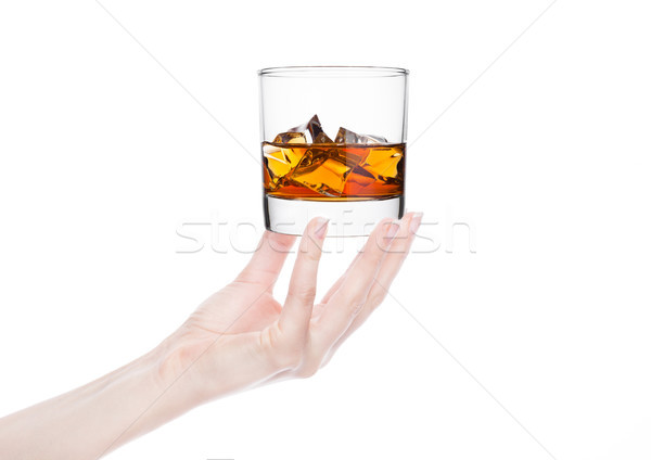 Female hand holding whiskey glass with ice Stock photo © DenisMArt