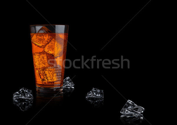 Orange energy soda drink glass with ice cubes Stock photo © DenisMArt