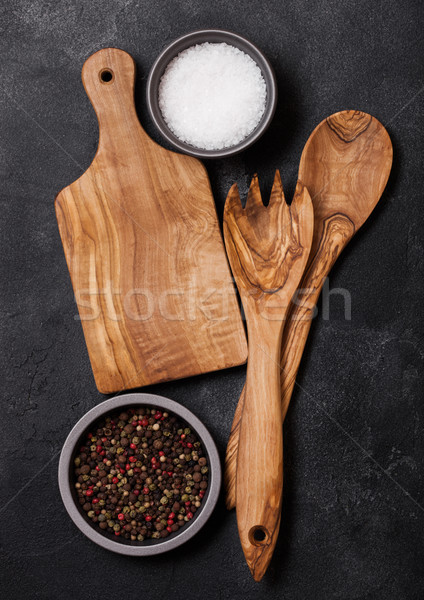 Olive wood kitchen utensils with chopping board stone table background. Top view.  Stock photo © DenisMArt