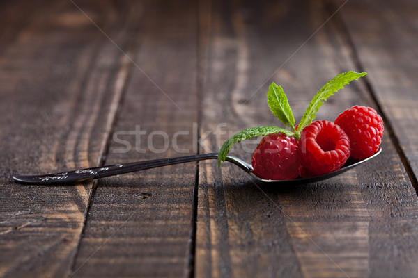 Raspberries on old spoon and mint on grunge wooden board Stock photo © DenisMArt