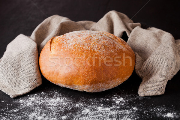 Freshly baked  bread with flour and kitchen towel Stock photo © DenisMArt