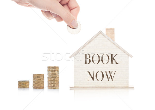 Stock photo: Wooden house model with coins next to it and hand