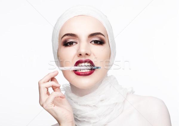 Beautiful model holding syringe in lips surgery Stock photo © DenisMArt