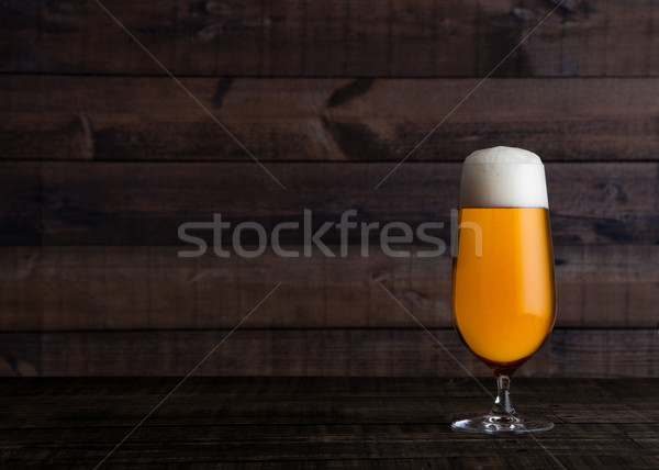 Glass of golden lager ale beer with foam on wood Stock photo © DenisMArt