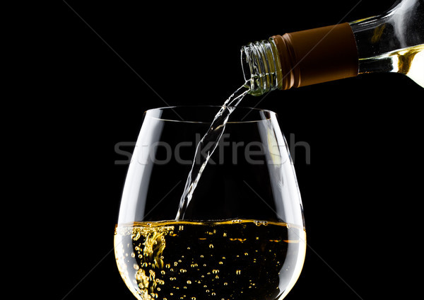 Pouring white wine from bottle to glass on black Stock photo © DenisMArt