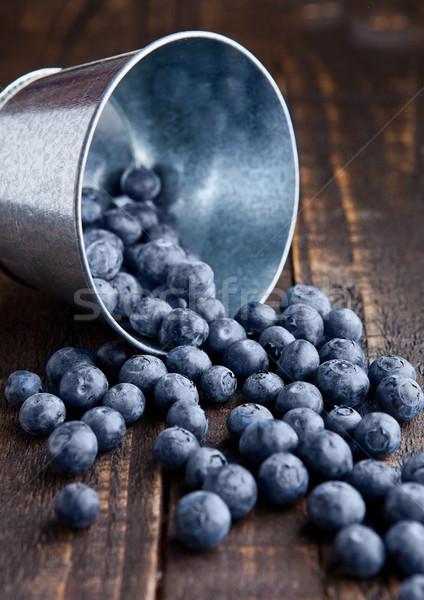 Blueberries in small steel bucket on grunge wooden board Stock photo © DenisMArt