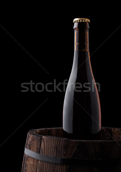 Cold bottle of craft beer on old wooden barrel Stock photo © DenisMArt
