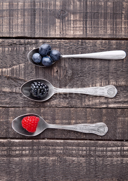Raspberry blueberry and blackberry on spoon and wooden table Stock photo © DenisMArt