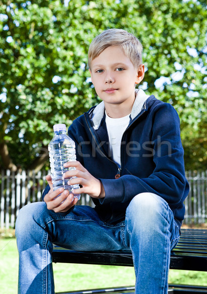 Young teenage boy with bottle of water in park Stock photo © DenisMArt