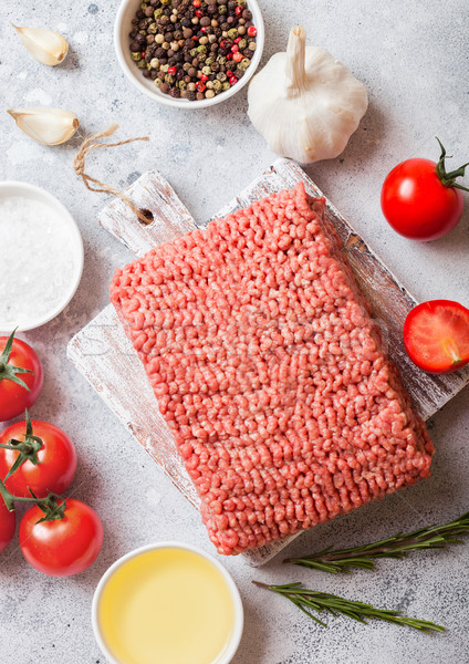 Raw minced homemade beef meat with spices and herbs. Top view.On top of chopping board and marble ki Stock photo © DenisMArt
