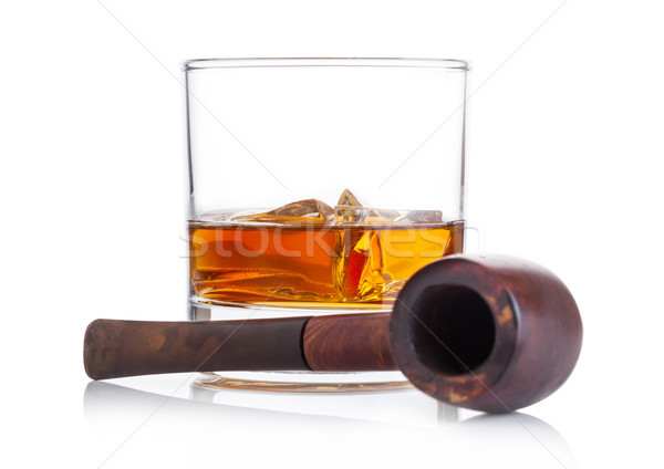 Glass of whiskey with ice cubes and vintage smoking pipe on white background. Cognac brandy drink Stock photo © DenisMArt