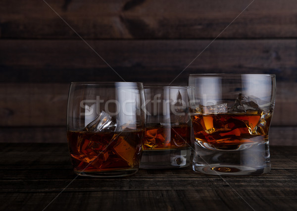 Glasses of whiskey with ice cubes on wooden table Stock photo © DenisMArt
