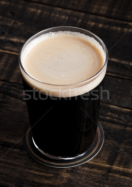 Glass of stout beer top with white foam Stock photo © DenisMArt