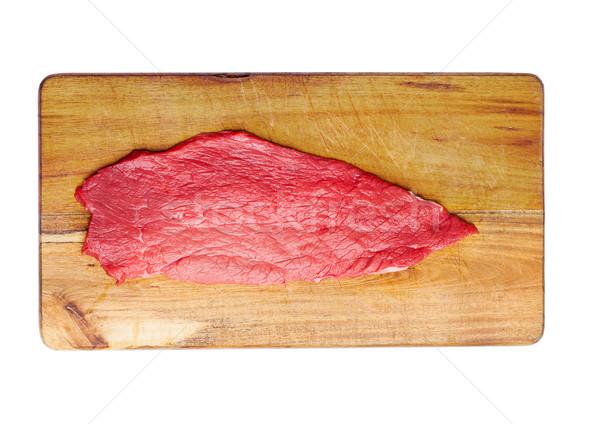 Fresh raw beef steak in black on wooden board Stock photo © DenisMArt
