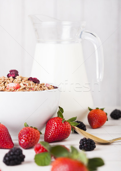 Bowl with cereal and fresh berries and jar of milk Stock photo © DenisMArt