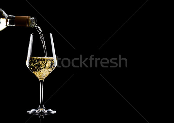 Pouring white wine from bottle to glass on black with space for your text Stock photo © DenisMArt