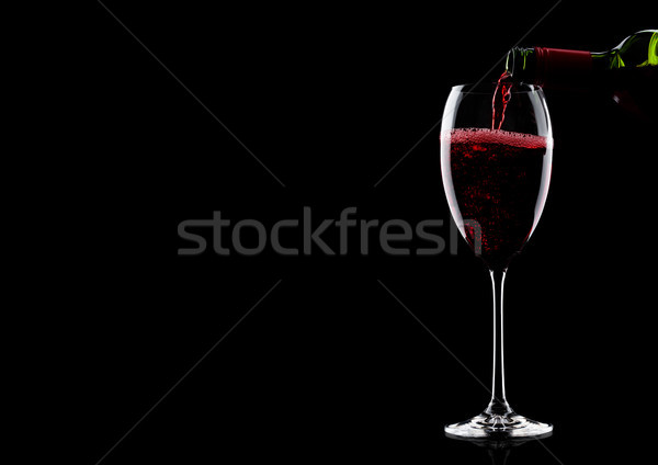 Pouring red wine from bottle to glass on black with space for your text Stock photo © DenisMArt