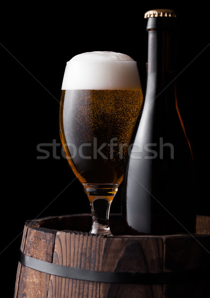Stock photo: Cold bottle and glass of craft beer on old barrel