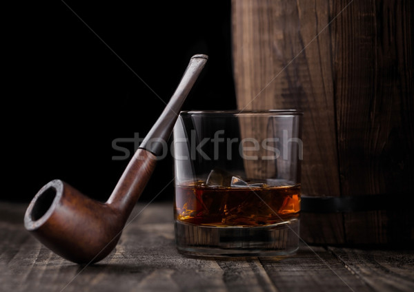 Stock photo: Glass of whiskey with ice cubes and vintage smoking pipe next to wooden barrel. Cognac brandy drink