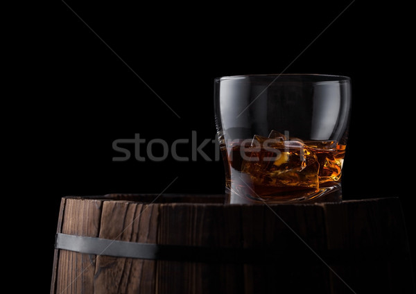 Glass of whiskey with ice cubes on top of wooden barrel. Cognac brandy drink Stock photo © DenisMArt
