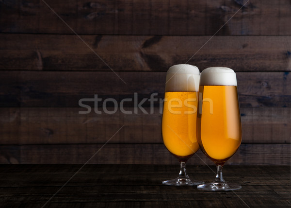 Glasses of golden lager ale beer with foam on wood Stock photo © DenisMArt