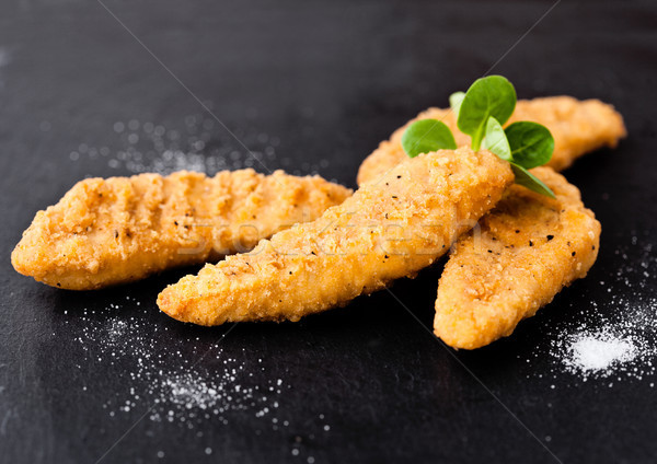Fried chicken dippers on stone board with salt Stock photo © DenisMArt