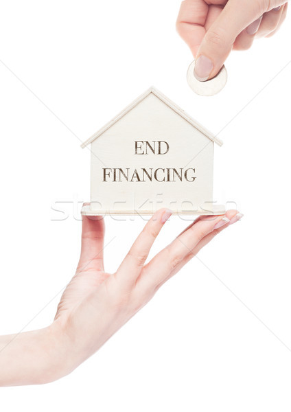 Hand holds wooden house model and hand with coin Stock photo © DenisMArt