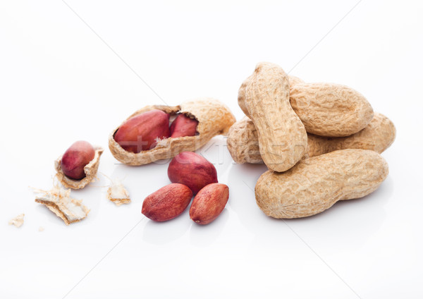 Raw peanuts with shell on white background Stock photo © DenisMArt
