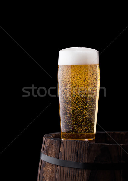 Stock photo: Cold glass of craft beer on old wooden barrel