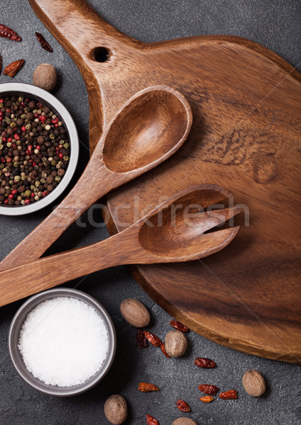 Vintage kitchen wooden utensils with chopping board on stone table background. Top view. Salt and pe Stock photo © DenisMArt