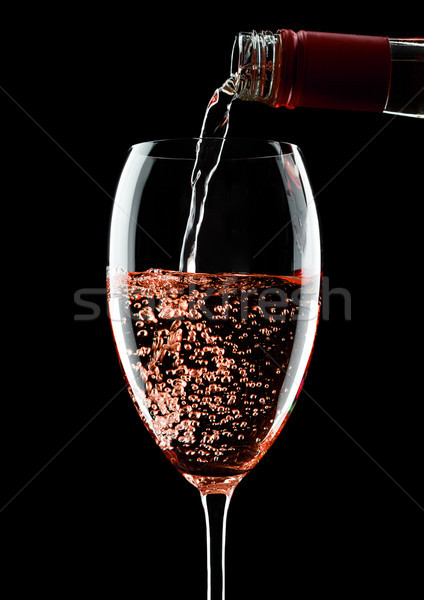 Pouring rose wine from bottle to glass on black Stock photo © DenisMArt