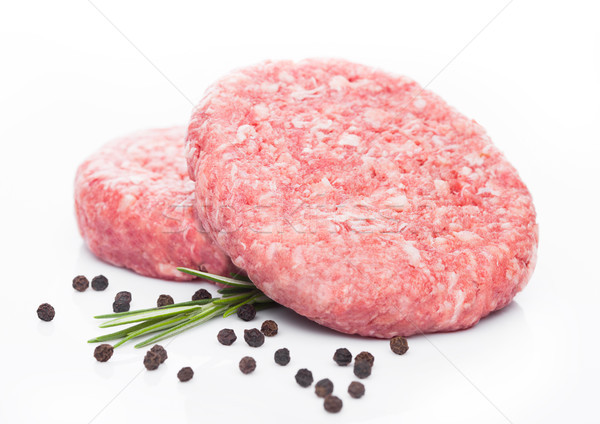 Raw fresh beef burgers with pepper and rosemarine Stock photo © DenisMArt