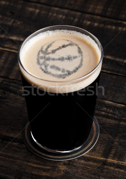 Glass of stout beer top with basketball shape Stock photo © DenisMArt