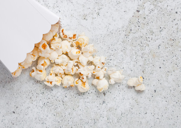 Paper container with fresh salted popcorn on stone Stock photo © DenisMArt
