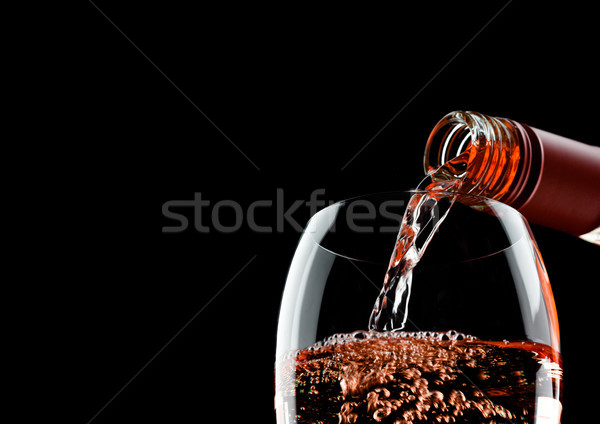 Pouring pink rose wine from bottle to glass on black  Stock photo © DenisMArt