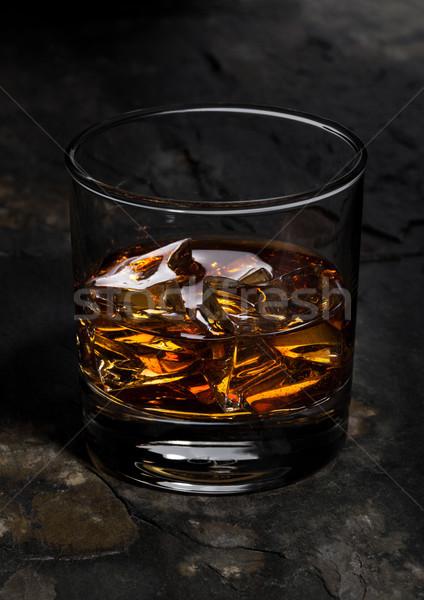 Elegant glass of whiskey with ice cubes on stone Stock photo © DenisMArt