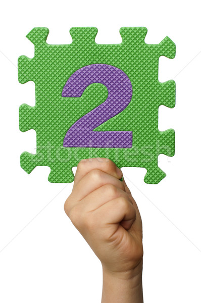Children hand holding the number Two. White isolated number Stock photo © deyangeorgiev