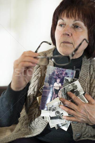 Idős nő öreg fotók néz szomorúság Stock fotó © deyangeorgiev