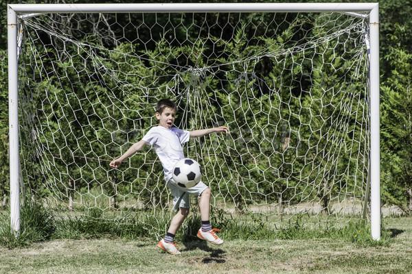 Child playing football in a stadium Stock photo © deyangeorgiev