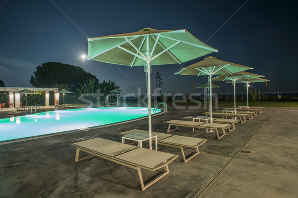 Pool, sunbeds and umbrellas at night Stock photo © deyangeorgiev