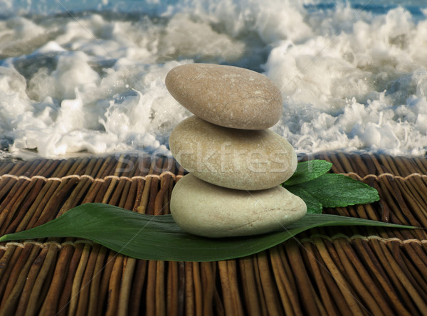 Stacked stones on wooden base for spa and green leafs Stock photo © deyangeorgiev